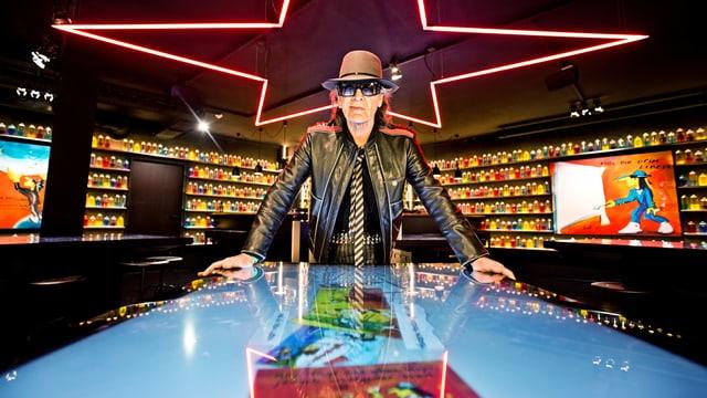 Udo Lindenberg steht in einem leuchtenden, Casino-ähnlichen Ausstellungsraum.