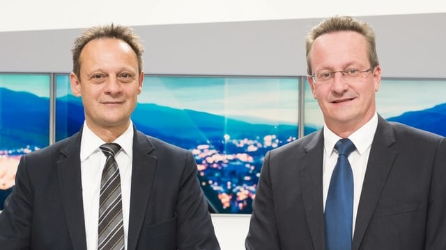 Die beiden Männer posieren in einem Fernsehstudio.