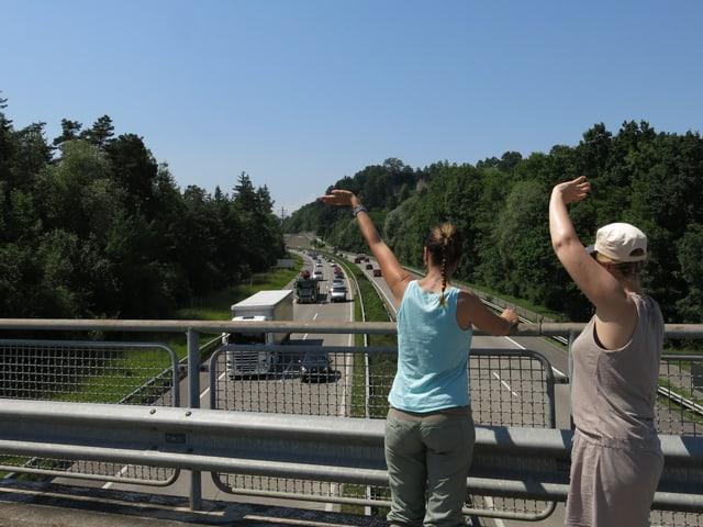 Zwei Frauen winken den Lastwagen auf der Autobahn.