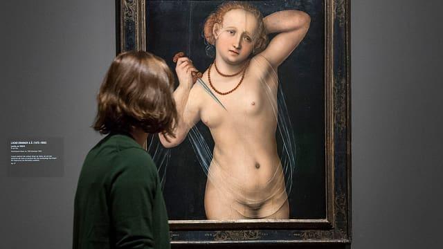 Eine Frau betrachtet ein Bild, auf dem eine nackte Frau mit einem Dolch zu sehen ist.