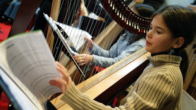 Ein Mädchen sitzt an einer Harfe und blättert ein Notenblatt um.