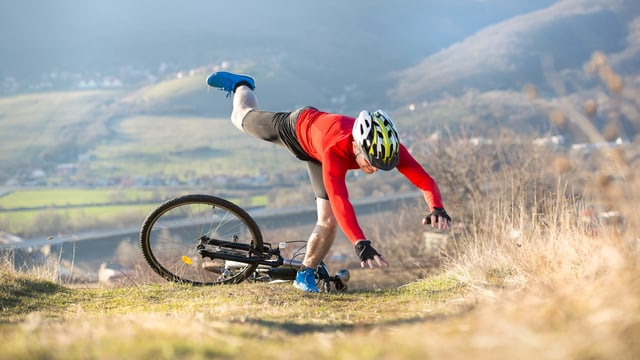 Mann, der mit Fahrrad sürzt