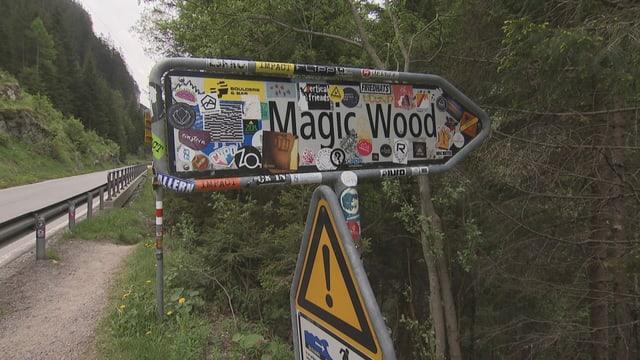 Wegweiser Magic Wood ist mit allerlei Stickern beklebt.