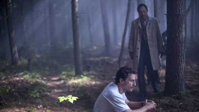 Zwei Männer in einem Wald. Einer kauert vorne im Bild, weiter hinten ein stehender Mann in einem Trenchcoat.