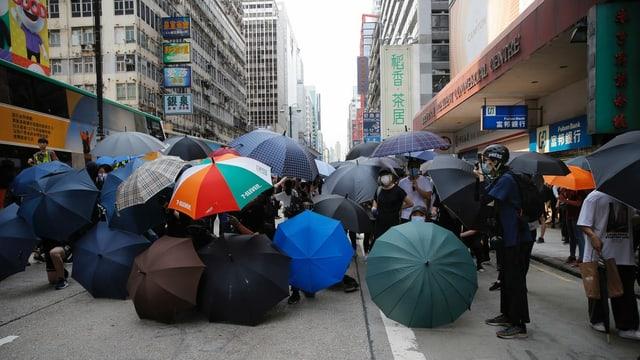 Protestierende mit farbigen Schirmen.