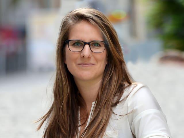 Eine junge Frau mit langen, geraden braunen Haaren und schwarzer Brille.