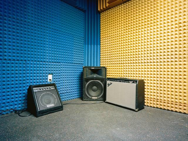 Drei Lautstärker auf dem Boden. Im Hintergrund sind Wände mit schalldämpfendem Schaumstoff.
