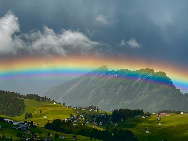Grosser Regenbogen mit klaren Farben vor Bergwelt.