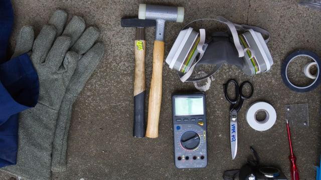 Nahaufnahme von Handschuhen, Hammer, Atemschutzmaske, Messgeräte etc.