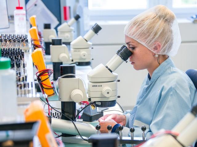 Frau mit weisser Schutzhaube am Mikroskop.