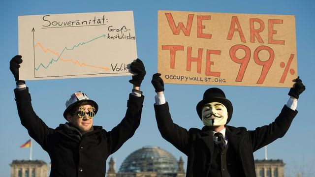 """Demonstranten mit Schildern, auf dem einen steht """"We are the 99%""""."""