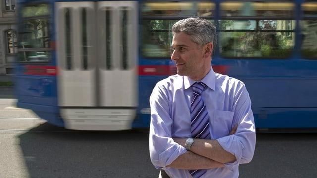 Ein Mann steht vor einem Tram.