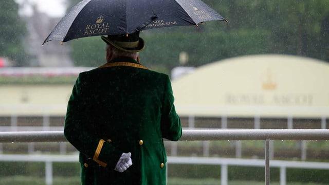 Ein Bediensteter steht mit weissen Handschuhen und Regenschirm da.