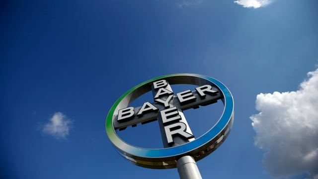 Das Bayer-Logo vor blauem Himmel mit Wölkchen.