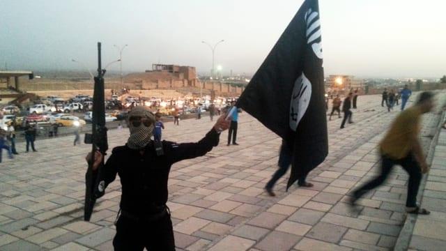 Ein Kämpfer des «Islamischen Staats» schwenkt in Mossul eine Flagge.