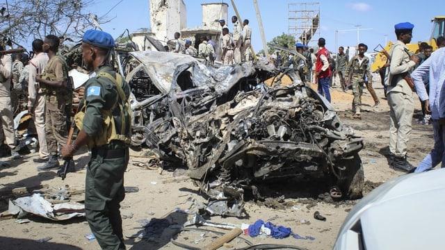 Ein Soldat steht vor völlig zerstörten Autos.