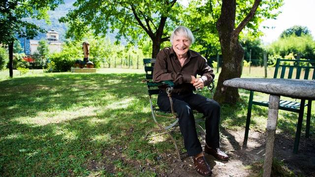 Ein Mann sitzt im Garten im Schatten der Bäume und lacht.