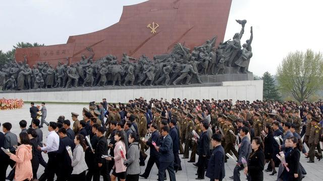 Personen vor einem Denkmal.