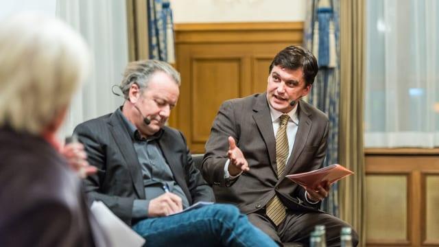 Mark Pieth hört zu und macht sich Notizen, Christoph Buser spricht und gestukuliert dazu
