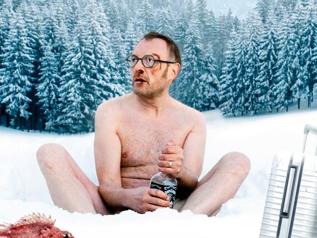 Josef Hader sitzt halbnackt im Schnee mit einer Flasche Whiskey, einem Fisch und einem Koffer.