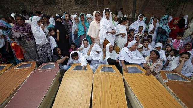 Frauen in Peshawar sitzen vor Särgen ihrer Liebsten. (reuters)