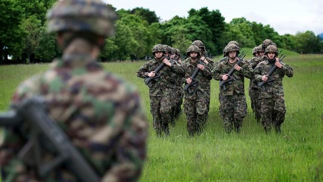 Rekruten laufen im Gleichschritt über ein Feld, im Vordergrund ein Vorgesetzter von hinten, im Hintergrund Waldrand.
