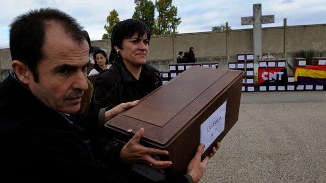 Ein Mann und eine Frau halten eine Holzkiste, dahinter ein Kreuz