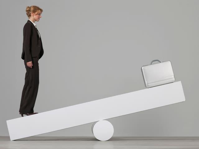 Eine Geschäftsfrau steht auf der linken Seite einer weissen, überdimensionierten Wippe - auf der rechten Seite steht ein Aktenkoffer.