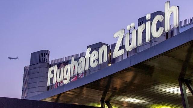 Das Bild zeigt das Hauptgebäude des Flughafens Zürich, am Abendhimmel ist ein startendes Flugzeug.