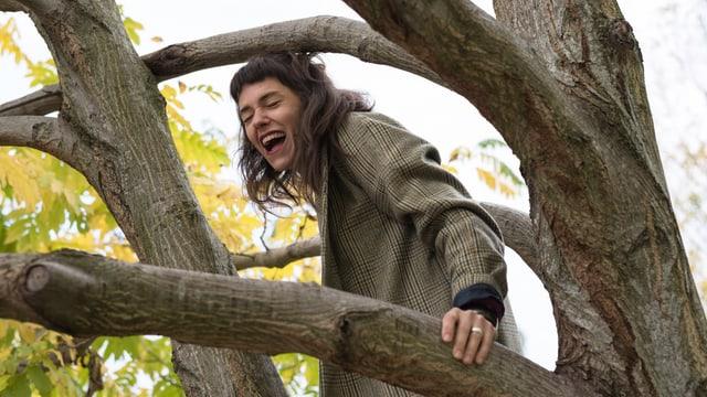 Spale klettert lachend auf einen Baum.