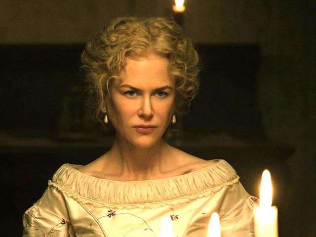 Eine Frau in weissem Kleid. Im Vordergrund drei Kerzen.