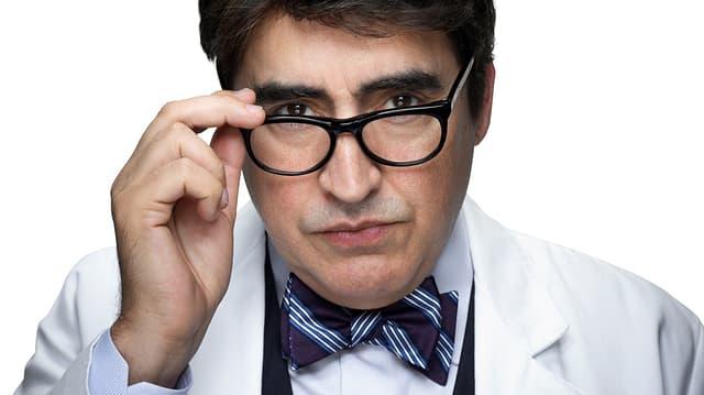Ein Mann in einem Ärztekittel mit Brille.
