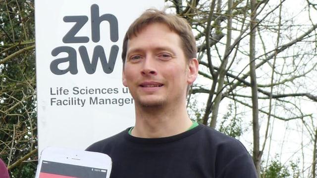 Ein Mann vor einem Schild der ZHAW