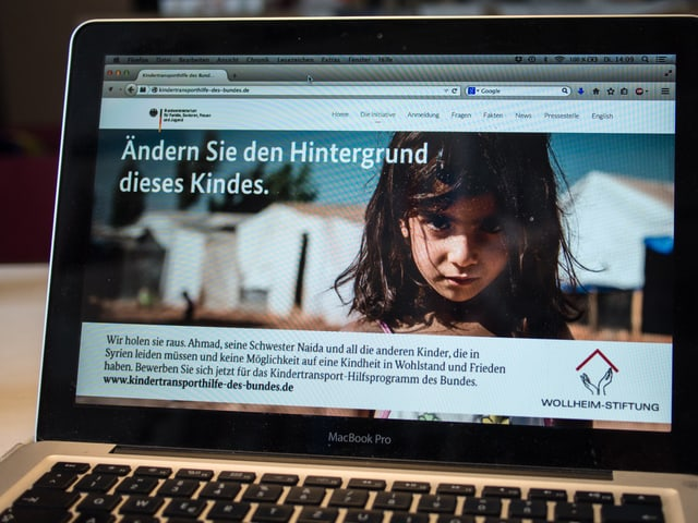 """Laptop, auf dem die Website zu sehen ist: Grosses Foto eines KIndes, darüber """"Ändern Sie den Hintergrund dieses Kindes""""."""