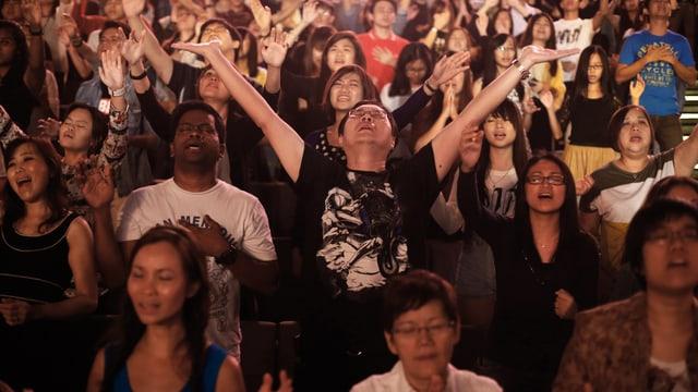 Eine Gruppe von Menschen, die betet. In der Mitte ein Mann, der beide Arme gegen den Himmel ausstreckt.