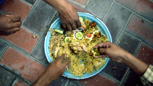 Vier Hände greifen nach einem Teller, auf dem ein Reisgericht angerichtet ist.