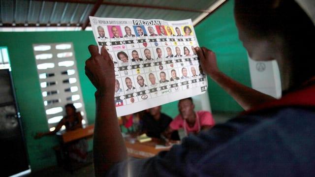 Ein Mann studiert die Liste mit den Kandidaten.