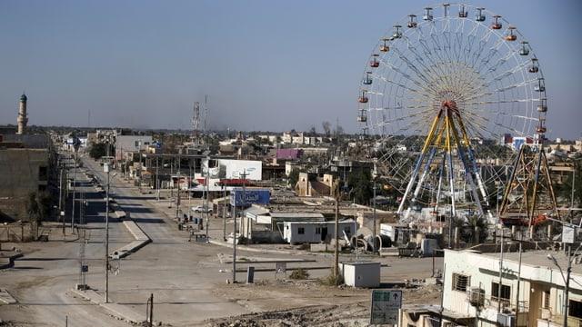 Blick auf eine verstaubte Stadt mit leeren Strassen, im Hintergrund ein Riesenrad.