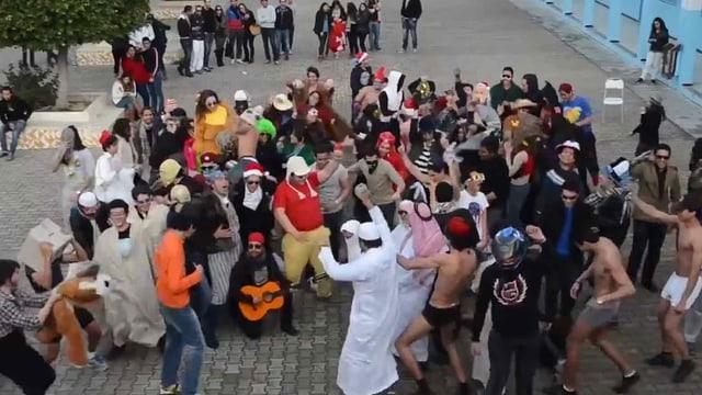 Gruppe von Leuten, zum Teil verkleidet, tanzen auf einem Platz