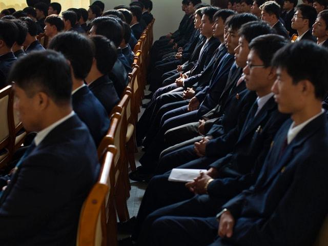 Studenten in dunklen Anzügen sitzen brav in mehreren Reihen auf Holzstühlen.