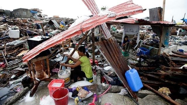 Eine Frau sitzt in einer vollständig zerstörten Siedlung und macht ihre Wäsche.