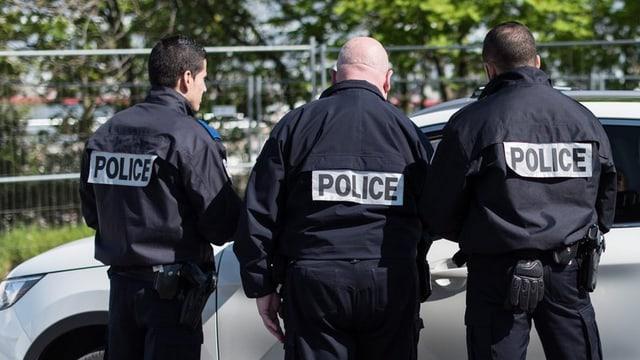 Trais policists en nair che controlleschan in auto.