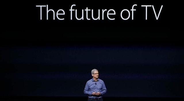 Ein Mann steht vor dunklem Hintergrund (Projektion) auf einer Bühne, dahinter steht «The future of TV».