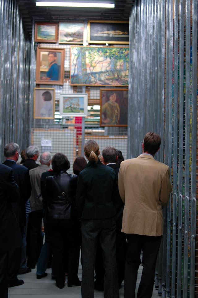 Ein Dutzend Menschen betrachtet Bilder an einer herausgezogenen Gitterwand im Archiv des Kunstmuseum Bern.