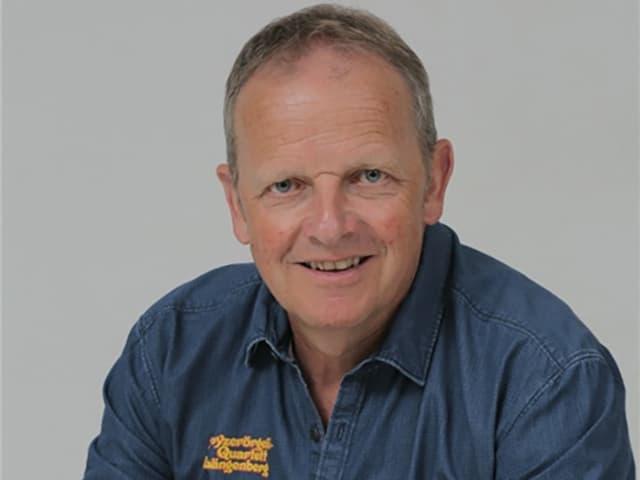 Porträt von einem Mann, der ein blaues Hemd trägt.