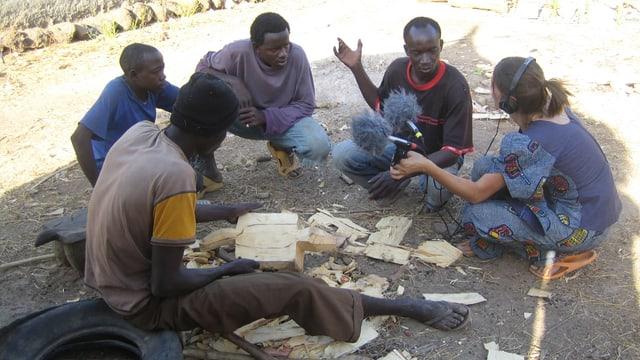 Afrikanische Männer sitzen im Halbkreis auf einer Strasse, ein Reporter mit Mikrofon macht Aufnahmen.