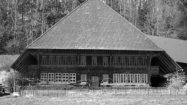 Bild in Graustufen von einem typischen Emmentaler Bauernhaus mit grossem, schützendem Dach.
