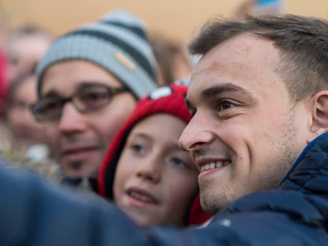 Xherdan Shaqiri macht ein Selfie mit einem Mann und dessen Sohn