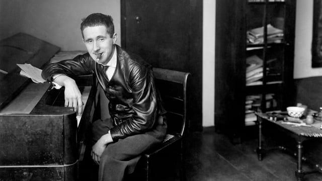 Bertolt Brecht in einer s/w-Fotografie, an ein Piano gelehnt, in Lederjacke, Zigarre im Mund.