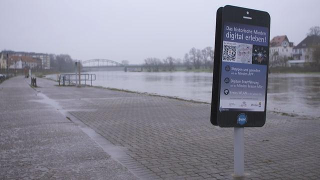 Ein Smartphone so gross wie ein Mensch am Flussufer von Monden. Es wirbt für die «Beacon-Mile».
